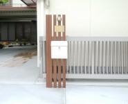 機能門柱 アルミ木調角柱に白いポストとブラス製のネームプレートとマリンランプ