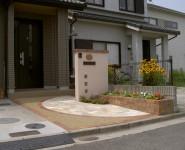 塗り門柱にレンガの植栽桝。1/2サークルがポイントのオープンタイプ外構